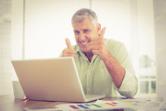 Smiling businessman gesturing thumbs up Stock Images