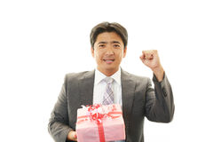 Smiling businessman with a gift Royalty Free Stock Image