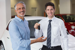 Smiling businessman giving car key to happy customer. At new car showroom Stock Image