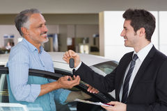 Smiling businessman giving car key to happy customer. At new car showroom Royalty Free Stock Photography