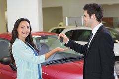 Smiling businessman giving car key to happy customer. At new car showroom Stock Photo