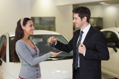 Smiling businessman giving car key to happy customer Stock Photos