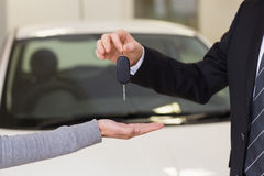 Smiling businessman giving car key to happy customer. At new car showroom Stock Photography