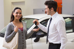 Smiling businessman giving car key to happy customer Stock Images