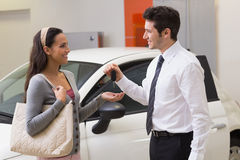 Smiling businessman giving car key to happy customer Royalty Free Stock Image