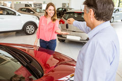 Smiling businessman giving car key to happy customer. At new car showroom Royalty Free Stock Photos