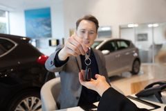 Smiling businessman giving car keys to female customer. In showroom Royalty Free Stock Photography