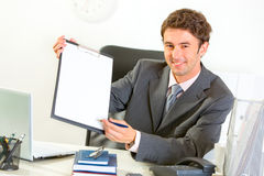 Smiling businessman giving clipboard for signing Royalty Free Stock Photo