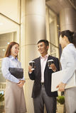 Smiling businessman giving coffee to two young businesswoman at the office Royalty Free Stock Photography