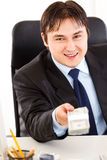 Smiling businessman giving dollar pack. Smiling  business man sitting at office desk and giving dollar pack Stock Image