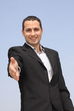 Smiling businessman giving hand for an handshake Stock Image
