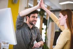 Smiling businessman giving high-five to female coworker Stock Photo