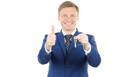 Smiling businessman giving keys of House, Office, Thumbs Up stock image