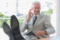 Smiling businessman giving ok sign Stock Photo