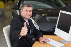 Smiling businessman giving thumbs up at his desk Stock Photo