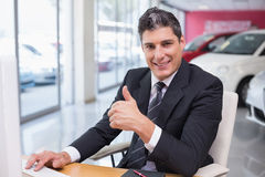Smiling businessman giving thumbs up at his desk Royalty Free Stock Photography