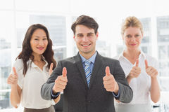 Smiling businessman giving thumbs up with his team Royalty Free Stock Photography
