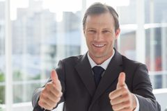 Smiling businessman giving thumbs up Stock Photos