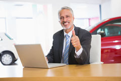 Smiling businessman giving thumbs up using his laptop. At new car showroom Royalty Free Stock Photography
