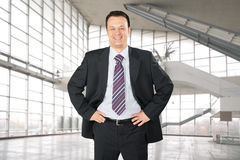 Smiling businessman in glass hall, collage Stock Image