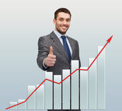 Smiling businessman with graph showing thumbs up Stock Photo