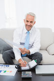 Smiling businessman with graphs and diary at home. Smiling mature businessman with graphs and diary sitting in the living room at home Royalty Free Stock Image