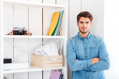 Smiling businessman with hands folded standing at office shelf Stock Image