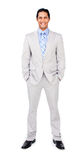 Smiling businessman with hands in pockets royalty free stock photography
