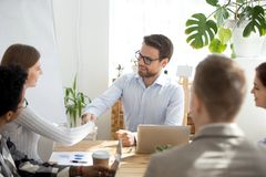Smiling businessman handshake female employee at meeting. Smiling millennial male ceo or boss shake hand of female employee get acquainted during office meeting royalty free stock image