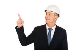 Smiling businessman with hard hat pointing up Royalty Free Stock Photography