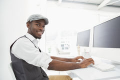 Smiling businessman with hat typing on keyboard Royalty Free Stock Image