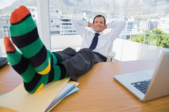 Smiling businessman having a nap with feet on the desk Stock Images