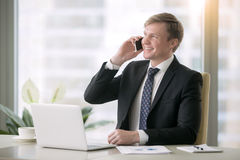 Smiling businessman having phonetalk. Young smiling handsome businessman working with laptop at the desk in modern office, talking on phone, planning future Royalty Free Stock Photo