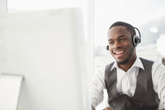 Smiling businessman with headset interacting. In his office Royalty Free Stock Photography