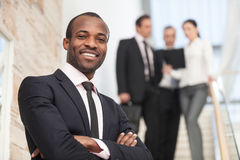Smiling businessman. With his colleagues in background Royalty Free Stock Image
