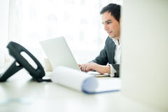Smiling Businessman at his Desk Chatting on Laptop Stock Image