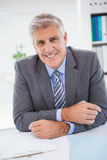 Smiling businessman at his desk Stock Photography