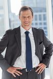 Smiling businessman with his hands on hips Royalty Free Stock Images