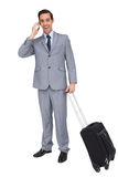 Smiling businessman with his luggage while phoning Stock Photos