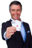 Smiling businessman holding all the aces Stock Images