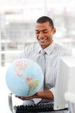 Smiling businessman holding aterrestrial globe stock images