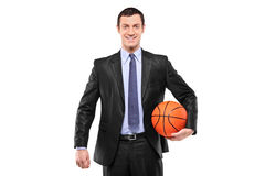 Smiling businessman holding a basketball Stock Images