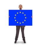 Smiling businessman holding a big card, flag of the European Uni Stock Images