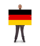 Smiling businessman holding a big card, flag of Germany Royalty Free Stock Image