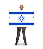 Smiling businessman holding a big card, flag of Israel Stock Photography