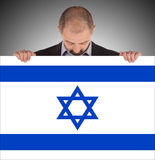 Smiling businessman holding a big card, flag of Israel Royalty Free Stock Images