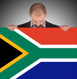 Smiling businessman holding a big card, flag of South Africa Stock Photo