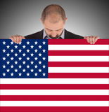 Smiling businessman holding a big card, flag of the United State Royalty Free Stock Photo