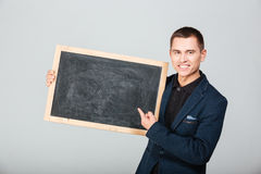 Smiling businessman holding blank board Stock Image