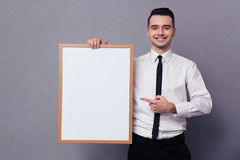Smiling businessman holding blank board Stock Images
